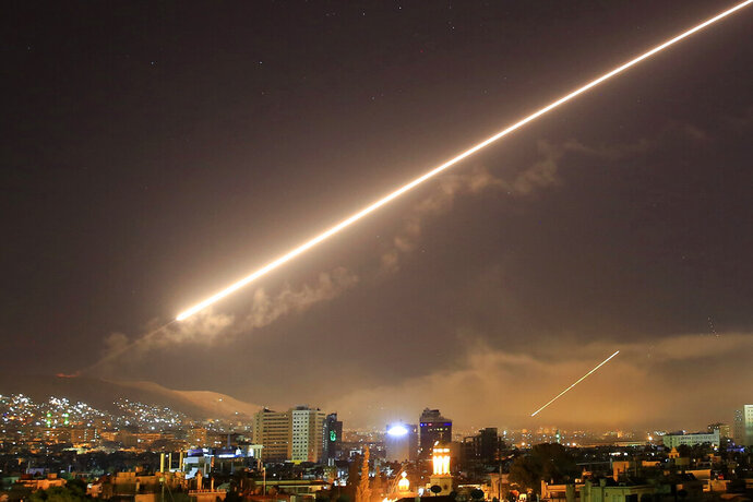 FILE - In this early Saturday, April 14, 2018 file photo, Damascus skies erupt with surface to air missile fire as the U.S. launches an attack on Syria targeting different parts of the Syrian capital Damascus, Syria.   A spokesman for the U.S.-led coalition said Friday, Jan. 11, 2019 that the process of withdrawal in Syria has begun, declining to comment on specific timetables or movements. (AP Photo/Hassan Ammar, File)