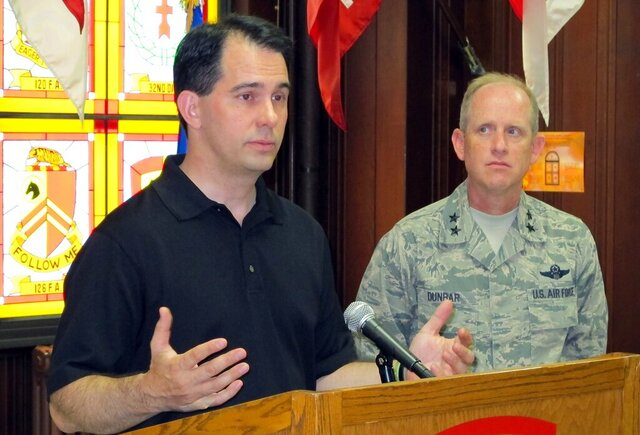 FILE - In this Sept. 7, 201 file photo, Wisconsin Army National Guard Maj. Gen. Don Dunbar, right, looks on as then Wisconsin Gov. Scott Walker talks to reporters in Milwaukee. Federal investigators plan to brief the Wisconsin National Guard's top commander this weekend on their seven-month review of the Guard's sexual assault reporting and investigation protocols. (AP Photo/Dinesh Ramde)