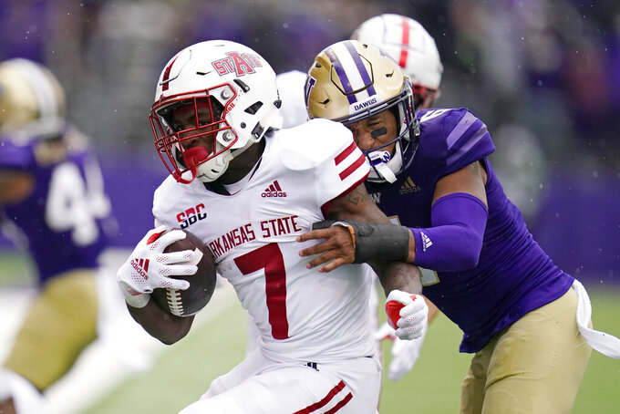 Arkansas State's Corey Rucker (7) is brought down by Washington's Cameron Williams in the second half of an NCAA college football game, Saturday, Sept. 18, 2021, in Seattle. (AP Photo/Elaine Thompson)
