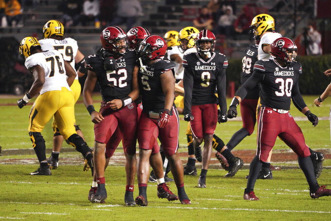 South Carolina defensive lineman Kingsley Enagbare (52) and lineman Keir Thomas (5) celebrate a defensive stop during the second half of an NCAA college football game against Missouri, Saturday, Nov. 21, 2020, in Columbia, S.C. (AP Photo/Sean Rayford)