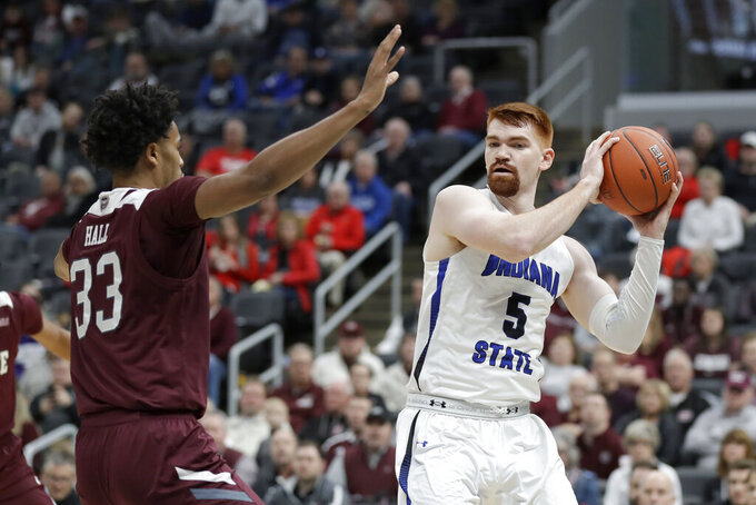Indiana State's Bronson Kessinger (5) looks to pass as Missouri State's Josh Hall (33) defends during the first half of an NCAA college basketball game in the quarterfinal round of the Missouri Valley Conference men's tournament Friday, March 6, 2020, in St. Louis. (AP Photo/Jeff Roberson)