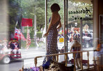 A mannequin stands in a storefront as a Fourth of July parade passes by Saturday, July 4, 2020, in Bristol, R.I. The town, which lays claim to the nation's oldest Independence Day celebration in the country, held a vehicle-only scaled down version of its annual parade Saturday due to the coronavirus pandemic. (AP Photo/David Goldman)