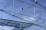 A construction worker is suspended above SoFi Stadium in Inglewood, Calif., on Wednesday, Jan. 22, 2020. The estimated $5 billion project is on schedule to open in July as the most expensive stadium in NFL history. (AP Photo/Greg Beacham)