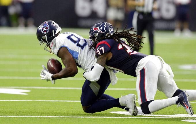 Tennessee Titans wide receiver Corey Davis, left, catches a pass as Houston Texans strong safety Jahleel Addae (37) defends during the first half of an NFL football game Sunday, Dec. 29, 2019, in Houston. (AP Photo/Michael Wyke)