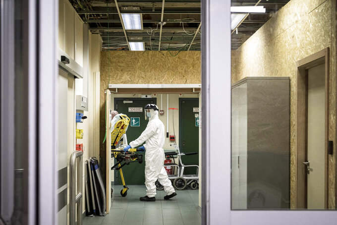 A member of medical staff wheels a patient on a bed as he arrives at the CHR CItadelle hospital in Liege, Belgium, Thursday, Oct. 29, 2020. Belgium has announced restrictive measures across the country in an effort to curb the fast-rising tide of COVID-19, coronavirus cases. (AP Photo/Valentin Bianchi)
