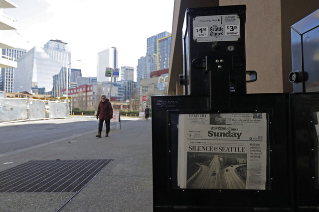 A woman walks near a Seattle Times newspaper box in front of the building that houses the Times' newsroom, Sunday, March 15, 2020 in Seattle, as the headline