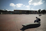 A person sits in an empty plaza amid the new coronavirus pandemic, in Bogota, Colombia, Tuesday, Jan. 5, 2021. Colombia's capital city is reimposing lockdown measures on Tuesday as COVID-19 infections rise around the country. (AP Photo/Ivan Valencia)