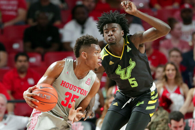 Houston forward Fabian White Jr. (35) looks to drive around South Florida guard Rashun Williams (5) during the first half of an NCAA college basketball game Sunday, Jan. 26, 2020, in Houston. (AP Photo/Michael Wyke)