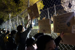 Demonstrators press against a perimeter security fence during a protest over the fatal shooting of Daunte Wright during traffic stop, outside the Brooklyn Center Police Department, Friday, April 16, 2021, in Brooklyn Center, Minn. (AP Photo/John Minchillo)