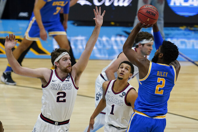 UCLA forward Cody Riley, right, shoots over Gonzaga forward Drew Timme, left, during the first half of a men's Final Four NCAA college basketball tournament semifinal game, Saturday, April 3, 2021, at Lucas Oil Stadium in Indianapolis. (AP Photo/Michael Conroy)