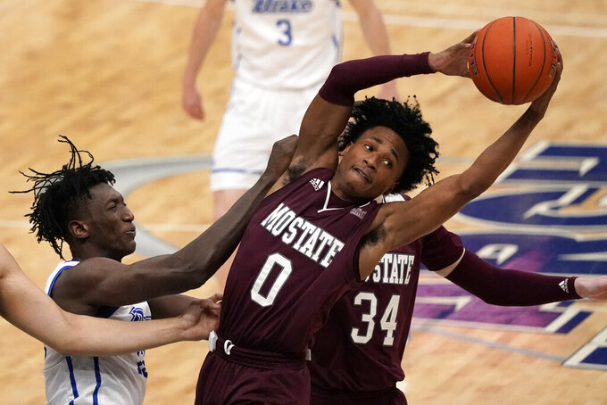 Missouri State's Demarcus Sharp (0) and Drake's Issa Samake, left, reach for a rebound during the first half of an NCAA college basketball game in the semifinal round of the Missouri Valley Conference men's tournament Saturday, March 6, 2021, in St. Louis. (AP Photo/Jeff Roberson)