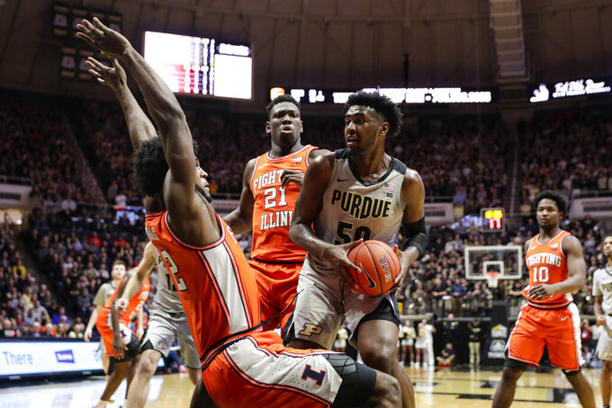 Illinois forward Kipper Nichols (2) tries to draw the charge from Purdue forward Trevion Williams (50) during the second half of an NCAA college basketball game in West Lafayette, Ind., Tuesday, Jan. 21, 2020. Illinois defeated Purdue 79-62. (AP Photo/Michael Conroy)