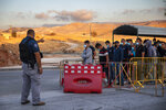 FILE - In this Tuesday, June 30, 2020, file photo,Palestinian laborers line up to cross a checkpoint at the entrance to the Israeli settlement of Maale Adumim, near Jerusalem. Israel's premier human rights group has begun describing both Israel and its control of the Palestinian territories as a single