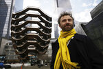 FILE - In this March 15, 2019, file photo, British designer Thomas Heatherwick poses in front of the Vessel on its opening day at Hudson Yards in New York.  Officials are evaluating the future of the 150-foot-tall piece of public art in New York City designed by Heatherwick after a string of suicides. Related, a company led by the billionaire Stephen Ross, and Heatherwick's studio had implemented a number of measures at the sculpture intended to prevent deaths. (AP Photo/Mark Lennihan, File)