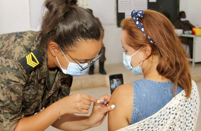 A soldier administers a dose of the Moderna COVID-19 vaccine to a woman, at the Assad Iben El Fourat school in Oued Ellil, outside Tunis, Sunday, Aug.15, 2021. Tunisia has launched its largest COVID-19 vaccination campaign as the country faces a surge of cases. Authorities aim to vaccinate over 1 million of people aged 40 and over in only one day, compared with 30,000 to 60,000 a day previously. (AP Photo/Hassene Dridi)