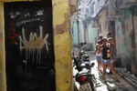 Residents walk near a doorway scared with bullet holes after a police raid against alleged drug traffickers in Rio de Janeiro, Brazil, Thursday, May 6, 2021. At least 25 people died including one police officer and 24 suspects, according to the press office of Rio's civil police. (AP Photo/Silvia Izquierdo)