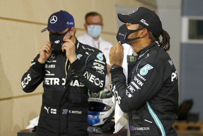 FILE - In this Saturday, Nov. 28, 2020 file photo Mercedes driver Lewis Hamilton of Britain, right, pole position, and Mercedes driver Valtteri Bottas of Finland, second position wear their masks after the qualifying session at the Formula One Bahrain International Circuit in Sakhir, Bahrain. World champion Lewis Hamilton tested positive for COVID-19 and will miss the Sakhir Grand Prix this weekend, his Mercedes-AMG Petronas F1 Team said Tuesday Dec. 1, 2020. (Hamad Mohammed, Pool via AP, File)