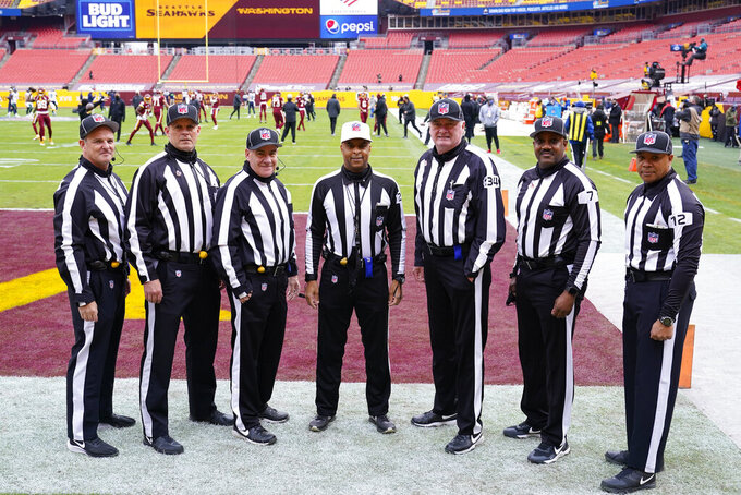 From l-r., Jim Quirk, Kevin Codey, Paul King, Adrian Hill, Ed Camp, Keith Washington, Greg Steed, pose for their Officials Portrait before the start of an NFL football game between the Seattle Seahawks and Washington Football Team, Sunday, Dec. 20, 2020, in Landover, Md. (AP Photo/Susan Walsh)