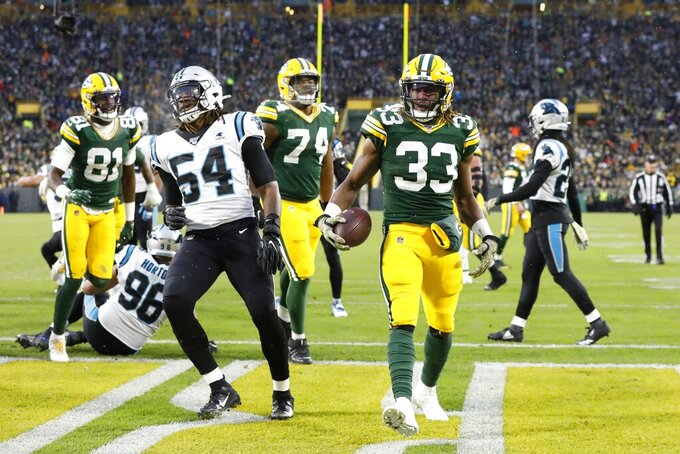 Green Bay Packers' Aaron Jones celebrates his touchdown run during the first half of an NFL football game against the Carolina Panthers Sunday, Nov. 10, 2019, in Green Bay, Wis. (AP Photo/Mike Roemer)