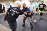 In this photo taken Sept. 10, 2019, Ryan Russo, second from left, goes through a drill with instructor Sean Fuller, left, during a defensive tactic training class at the American Medical Response training center in Clackamas, Ore. Paramedics in Portland are undergoing mandatory training in defensive tactics after a rash of high-profile attacks against them as they respond to 911 calls for people in a mental health or drug-related crisis. (AP Photo/Steve Dykes)
