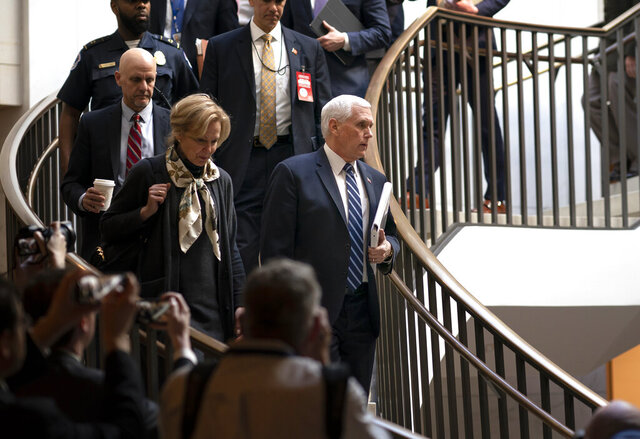 Vice President Mike Pence, center, joined at left by Dr. Deborah Birx, the coronavirus response coordinator, arrives at the Capitol to brief House members on the COVID-19 outbreak, in Washington, Wednesday, March 4, 2020. Congressional negotiators have reached agreement on an $8.3 billion bill to fund the government's response to the public health emergency. (AP Photo/J. Scott Applewhite)