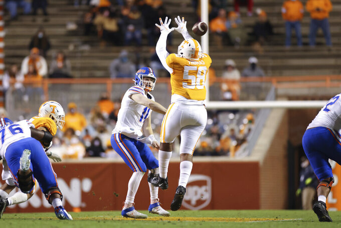 Florida quarterback Kyle Trask (11) passes the ball while being pressured by Tennessee defensive lineman Omari Thomas (58) during the second half of an NCAA college football game Saturday, Dec. 5, 2020, in Knoxville, Tenn. (Randy Sartin/Knoxville News Sentinel via AP)