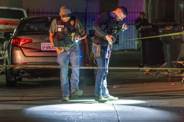Tulare Police investigate a shooting Wednesday, March 4, 2020 in Tulare, Calif.  The shooting occurred Wednesday night as a group of more than 60 people gathered at an apartment complex following the burial of a man who died in a car crash. (Ron Holman/The Times-Delta via AP)
