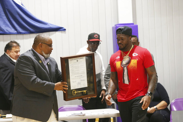 In this Feb. 20, 2020, photo, Houma native Elijah McGuire, right, a Super Bowl champion running back with the Kansas City Chiefs, receives a key to the city from Terrebonne Parish Councilman John Navy during a ribbon-cutting ceremony at the renovated Mechanicville Gym in Houma, La. (Chris Singleton/The Courier via AP)