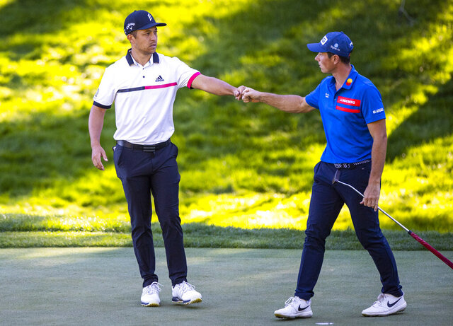 Xander Schauffele, left, fist bumps with Viktor Hovland after finishing the second round of the CJ Cup golf tournament at the Shadow Creek Golf Course, Friday, Oct. 16, 2020, in North Las Vegas. (Chase Stevens/Las Vegas Review-Journal via AP)