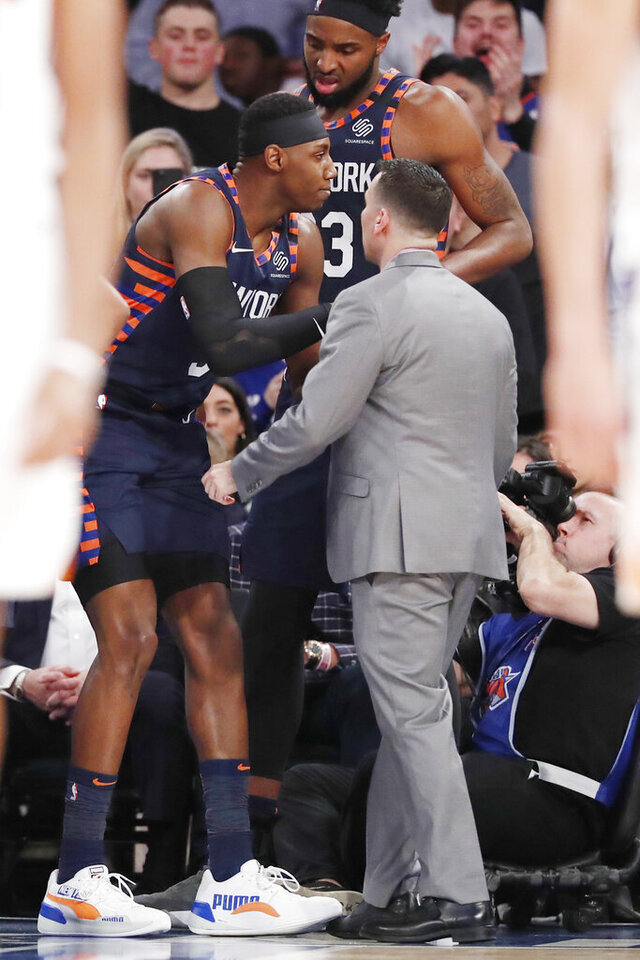 New York Knicks center Mitchell Robinson, above, consoles Knicks guard RJ Barrett, left, as a Knicks employee helps Barrett off the court after Barrett sprained his ankle during the second half of an NBA basketball game against the Phoenix Suns in New York, Thursday, Jan. 16, 2020. The Suns defeated the Knicks 121-98. (AP Photo/Kathy Willens)