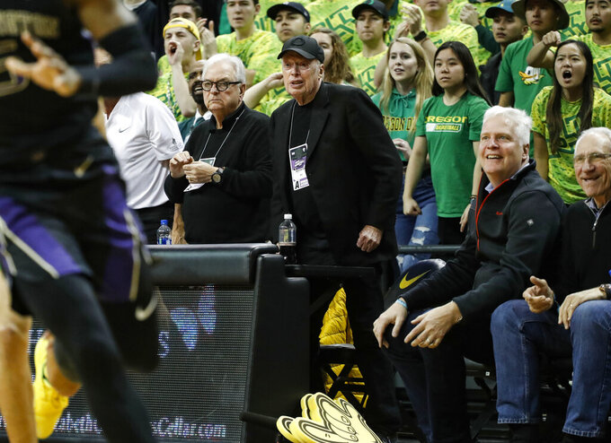 Nike co-founder Phil Knight, at center with dark cap, reacts as Oregon comes back against Washington during an NCAA college basketball game Thursday, Jan. 24, 2019, in Eugene, Ore. (AP Photo/Thomas Boyd)