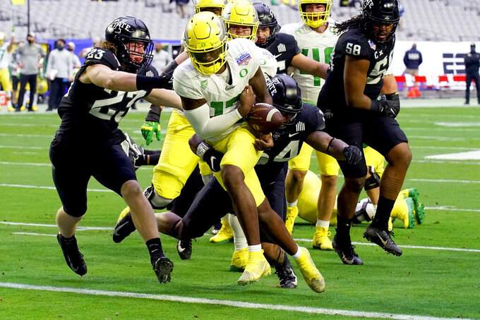 Oregon quarterback Anthony Brown (13) scores a touchdown as Iowa State linebacker O'Rien Vance (34) and linebacker Mike Rose (23) defends and during the first half of the Fiesta Bowl NCAA college football game, Saturday, Jan. 2, 2021, in Glendale, Ariz.(AP Photo/Rick Scuteri)