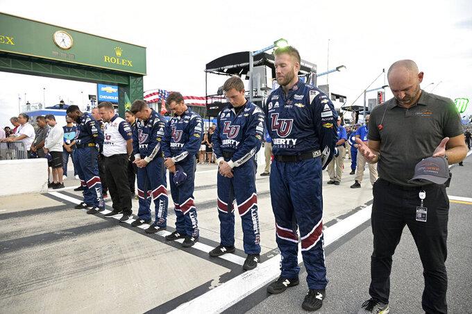 Crew members stand on pit road before a NASCAR Cup Series auto race at Daytona International Speedway, Saturday, Aug. 28, 2021, in Daytona Beach, Fla. (AP Photo/Phelan M. Ebenhack)