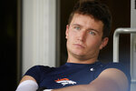 Denver Broncos quarterback Drew Lock sits off to the side and listens to teammate Justin Simmons talk to reporters after taking part in drills at an NFL football training camp at team headquarters Wednesday, July 28, 2021, in Englewood, Colo. (AP Photo/David Zalubowski)