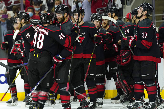 Carolina Hurricanes left wing Jordan Martinook (48) hugs center Jordan Staal (11) after Staal scored during overtime in Game 5 of an NHL hockey Stanley Cup first-round playoff series against the Nashville Predators in Raleigh, N.C., Tuesday, May 25, 2021. (AP Photo/Gerry Broome)
