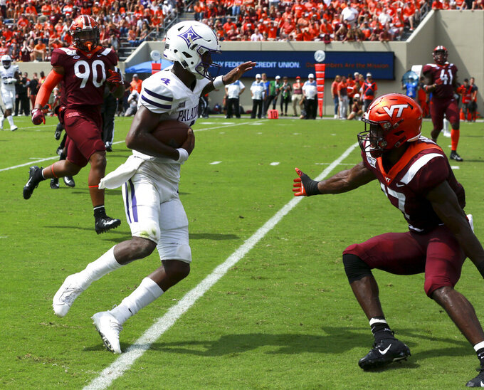 Furman quarterback Darren Grainger (4) eludes Virginia Tech defender Divine Deablo (17) for a 15-yard touchdown during the first half of an NCAA college football game, Saturday, Sept. 13, 2019, in Blacksburg Va. (Matt Gentry/The Roanoke Times via AP)