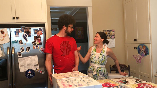 In this April 26, 2020, image from video provided by Whitney Rutz, Whitney Rutz, right, and husband, Paul, stand near several decorated boxes to hold large cinnamon rolls in their home in Portland, Ore. The Rutz family has helped raise thousands of dollars for Oregon Food Bank. (Whitney Rutz via AP)