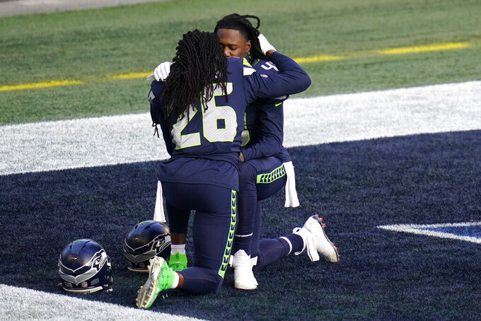 Seattle Seahawks cornerback Shaquill Griffin (26) hugs his brother, linebacker Shaquem Griffin (49), right, as they kneel in the end zone before an NFL football game against the Los Angeles Rams, Sunday, Dec. 27, 2020, in Seattle. (AP Photo/Elaine Thompson)