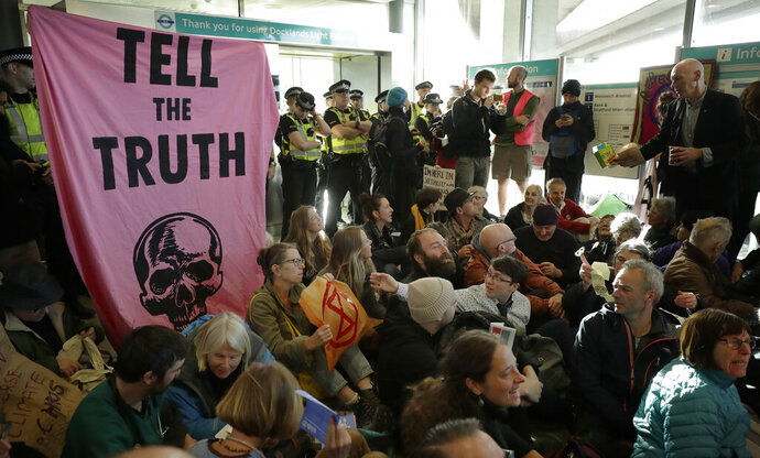Police Officers stand guard as Extinction Rebellion demonstrators peacefully block an entrance at City Airport in London, Thursday, Oct. 10, 2019. Some hundreds of climate change activists are in London during a fourth day of world protests by the Extinction Rebellion movement to demand more urgent actions to counter global warming. (AP Photo/Matt Dunham)