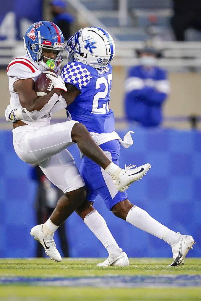 Mississippi wide receiver Elijah Moore (8) is tackled by Kentucky defensive back Tyrell Ajian (23) during the second half of an NCAA college football game, Saturday, Oct. 3, 2020, in Lexington, Ky. (AP Photo/Bryan Woolston)