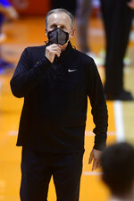 Tennessee coach Rick Barnes adjusts his mask during the team's NCAA college basketball game against Kansas in Knoxville, Tenn., Saturday, Jan. 30, 2021. (Caitie McMekin/Knoxville News Sentinel via AP, Pool)