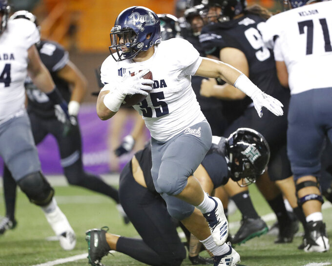 Nevada running back Toa Taua (35) breaks through a Hawaii defense during the third quarter at an NCAA college football game Saturday, Oct. 20, 2018, in Honolulu. (AP Photo/Marco Garcia)