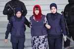 Vietnamese Doan Thi Huong, center, is escorted by police as she leaves Shah Alam High Court in Shah Alam, Malaysia, Thursday, March 14, 2019. Malaysia's attorney general ordered the murder case to proceed against the Vietnamese woman accused in the killing of the North Korean leader's estranged half brother, prosecutors said in court Thursday. (AP Photo/Vincent Thian)