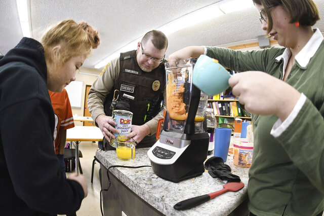 Morton County Deputy Sheriff David Tomlinson helps students Erica Simpson, 16, left, and Sabrina Doll, 15, make a slushy juice drink during his visit on Jan. 30, 2020 to New Salem High School in New Salem, North Dakota.  (Mike McCleary/The Bismarck Tribune via AP)