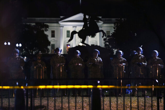 With the White House in the background, a line of police forms behind a fence in Lafayette Park as demonstrators gather to protest the death of George Floyd, Tuesday, June 2, 2020, in Washington. Floyd died after being restrained by Minneapolis police officers. (AP Photo/Evan Vucci)