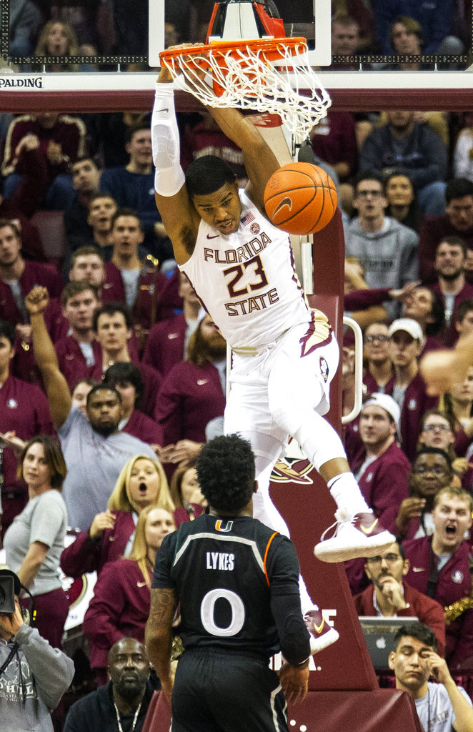 Florida State guard J.J. Walker watches Miami guard Chris Lykes as he dunks the ball in the first half of an NCAA college basketball game in Tallahassee, Fla., Wednesday, Jan. 9, 2019. (AP Photo/Mark Wallheiser)
