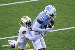 North Carolina wide receiver Dyami Brown (2) catches a pass as Notre Dame cornerback TaRiq Bracy (28) defends during the first half of an NCAA college football game in Chapel Hill, N.C., Friday, Nov. 27, 2020. (AP Photo/Gerry Broome)