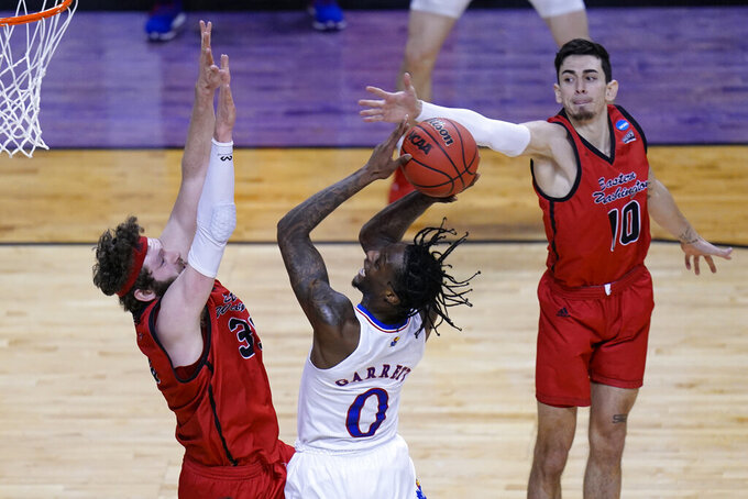 Kansas guard Marcus Garrett (0) goes up for a shot as Eastern Washington forward Tanner Groves (35) and teammate Jacob Davison (10) defend during the second half of a first-round game in the NCAA college basketball tournament at Farmers Coliseum in Indianapolis, Saturday, March 20, 2021. (AP Photo/AJ Mast)