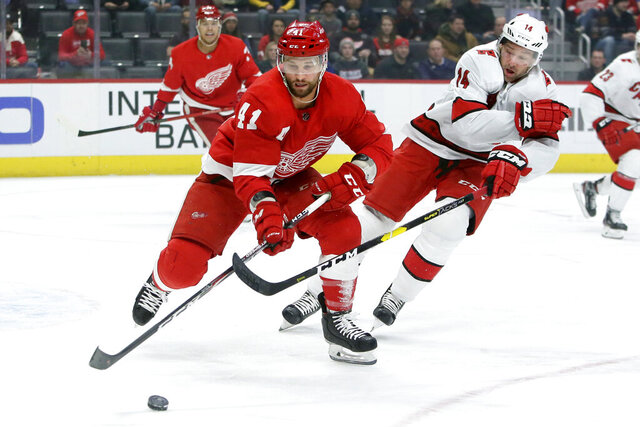 FILE - In this March 10, 2020, file photo, Carolina Hurricanes right wing Justin Williams (14) tries to steal the puck form Detroit Red Wings center Luke Glendening (41) during the first period of an NHL hockey game in Detroit. Williams retired Thursday, Oct. 8, 2020, after 19 NHL seasons that included winning the Stanley Cup in 2006 with Carolina along with two more with the Los Angeles Kings in 2012 and 2014. (AP Photo/Duane Burleson, File)