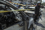 FILE - In this June 29, 2015 file photo, a policeman stands guard at the site of a car bombing that killed Egypt's top prosecutor, Hisham Barakat, in Cairo. On Wednesday, Feb. 20, 2019 Egypt executed nine suspected Muslim Brotherhood members convicted of involvement in the 2015 assassination of Barakat, security officials said. The nine were found guilty of taking part in the bombing that killed Barakat, the first assassination of a senior official in Egypt in a quarter century. (AP Photo/Eman Helal, File)